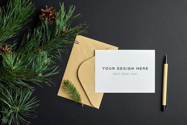 Maqueta de tarjeta de felicitación de navidad con ramas de pino sobre fondo de papel oscuro
