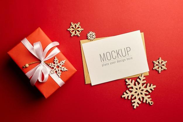 Maqueta de tarjeta de felicitación navideña con caja de regalo y adornos de madera