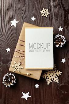 Maqueta de tarjeta de felicitación navideña con caja de regalo, piñas y adornos de madera