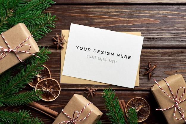 Maqueta de tarjeta de felicitación navideña con cajas de regalo, naranjas secas y ramas de pino