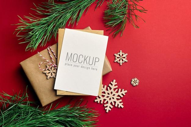 Maqueta de tarjeta de felicitación navideña con cajas de regalo y ramas de pino