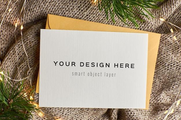 Maqueta de tarjeta de felicitación navideña con luces y ramas de pino decoradas