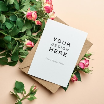 Maqueta de tarjeta de felicitación con sobre y flores rosas