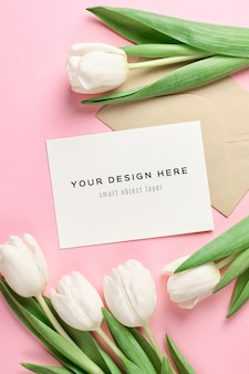 Maqueta de tarjeta de felicitación con sobre y flores de tulipán blanco sobre fondo rosa