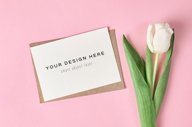 Maqueta de tarjeta de felicitación con sobre y tulipán blanco sobre fondo rosa