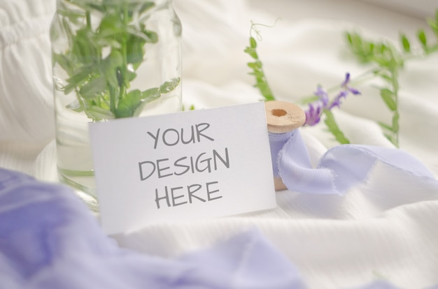 Maqueta de tarjeta con flores violetas y delicadas cintas de seda sobre un fondo blanco.