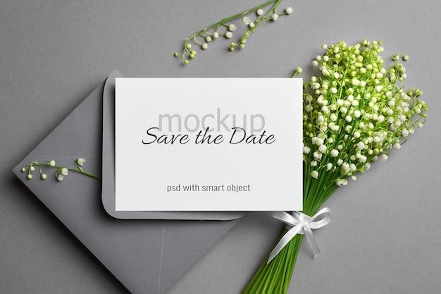 Maqueta de tarjeta de invitación de boda con sobre y ramo de flores de lirio de los valles blancos