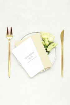 Maqueta de tarjeta de invitación en plato y cubiertos de oro