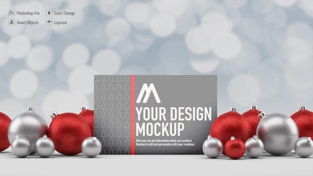 Maqueta de tarjeta de navidad junto a bolas de navidad y fondo borroso