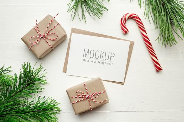 Maqueta de tarjeta navideña con cajas de regalo, bastón de caramelo y ramas de pino