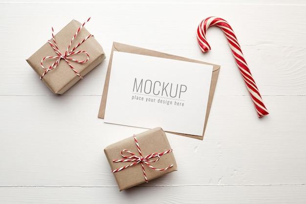 Maqueta de tarjeta navideña con cajas de regalo y bastón de caramelo