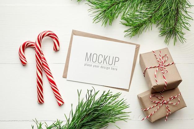 Maqueta de tarjeta navideña con cajas de regalo, bastones de caramelo y ramas de pino