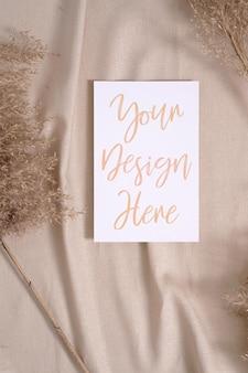 Maqueta de tarjeta de papel en blanco blanco con pasto seco de la pampa sobre un textil de color beige