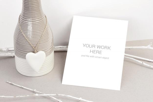 Maqueta de tarjeta con vasa de cerámica y corazón.