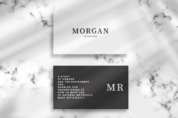 Maqueta de tarjeta de visita en blanco y negro sobre fondo de mármol