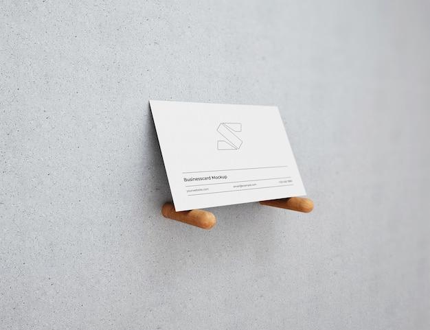 Maqueta de tarjeta de visita en fondo claro con palos de madera