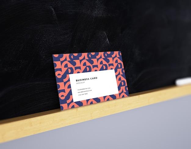 Maqueta de tarjeta de visita en el fondo oscuro de la pizarra con estante de madera y tiza