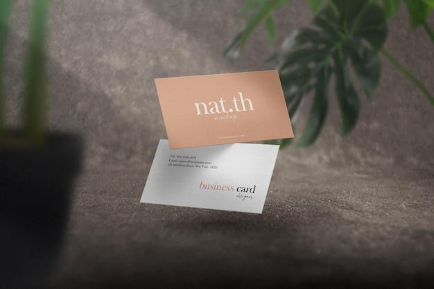 Maqueta de tarjeta de visita mínima limpia en alfombra con fondo de hojas