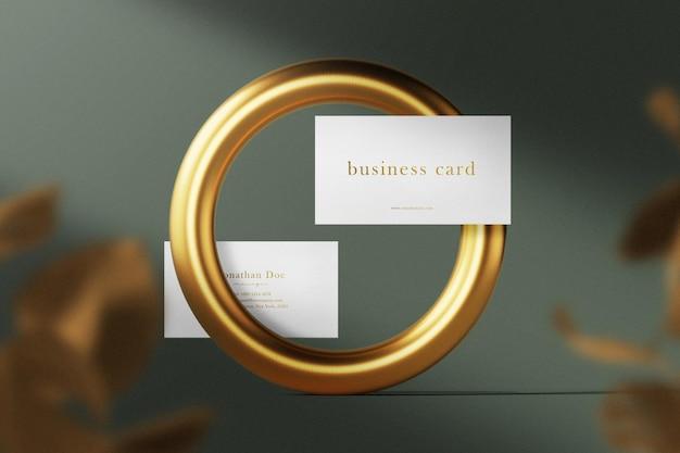 Maqueta de tarjeta de visita mínima limpia flotando en anillo de oro con hojas