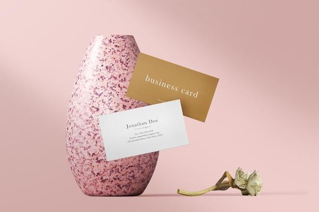 Maqueta de tarjeta de visita mínima limpia flotando en un jarrón con flor seca