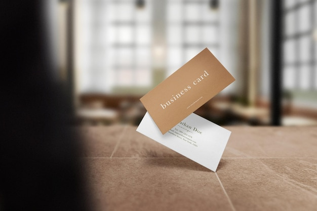 Maqueta de tarjeta de visita mínima limpia flotando en la mesa superior en la cafetería