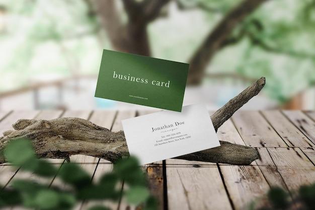Maqueta de tarjeta de visita mínima limpia flotando en una rama con hojas