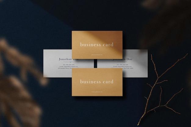 Maqueta de tarjeta de visita mínima limpia en el fondo con hojas de otoño y palo