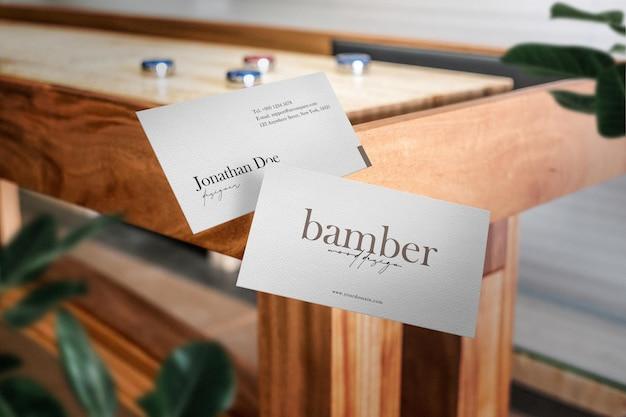Maqueta de tarjeta de visita mínima limpia junto a la mesa de madera