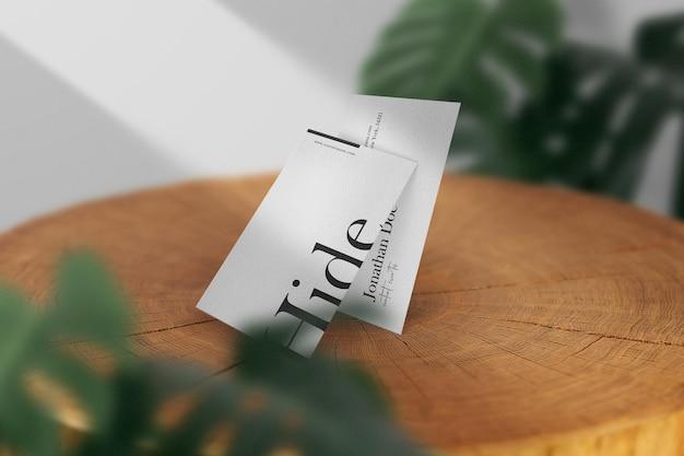 Maqueta de tarjeta de visita mínima limpia en madera con fondo de hojas. archivo psd.