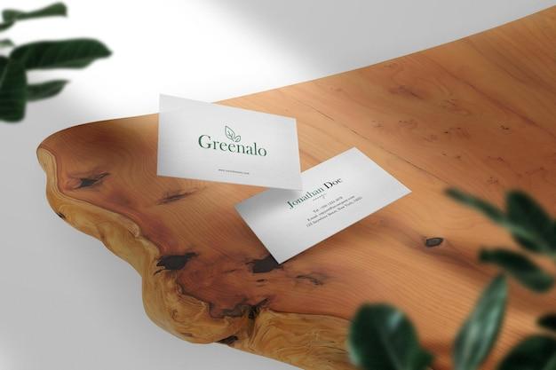 Maqueta de tarjeta de visita mínima limpia en mesa de madera con fondo de hojas. archivo psd.