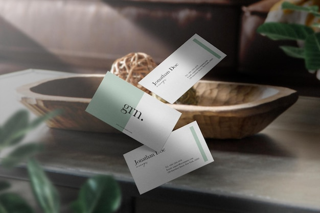 Maqueta de tarjeta de visita mínima limpia en mesa de madera con hojas y fondo claro