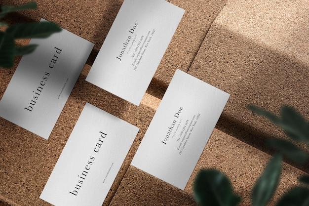 Maqueta de tarjeta de visita mínima limpia en piso de bloque y piedra