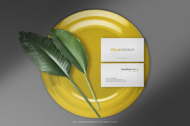 Maqueta de tarjeta de visita mínima limpia en placa de color con hojas.