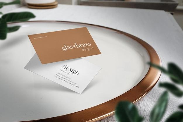 Maqueta de tarjeta de visita mínima limpia en plato blanco con sombra de ventana
