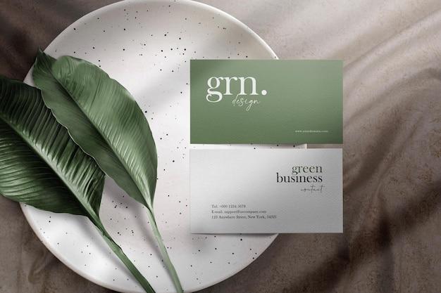 Maqueta de tarjeta de visita mínima limpia en un plato con hojas y fondo de tela