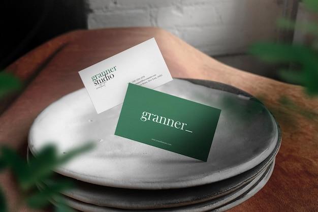 Maqueta de tarjeta de visita mínima limpia en platos con luz y sombra