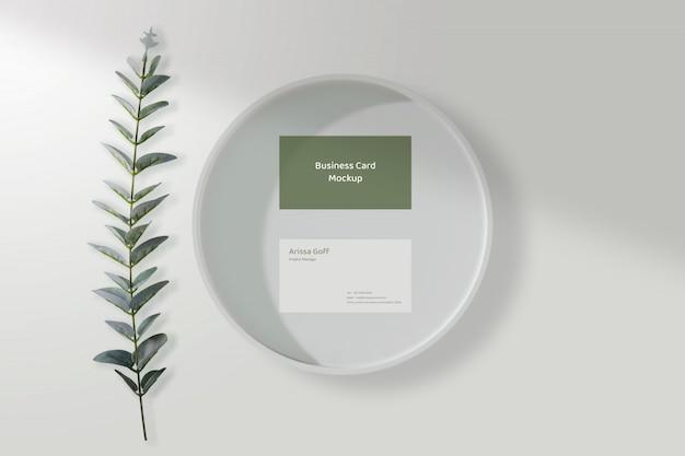 Maqueta de tarjeta de visita mínima en el plato blanco