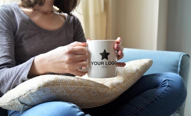 Maqueta para taza agarrada a mano en un ambiente acogedor