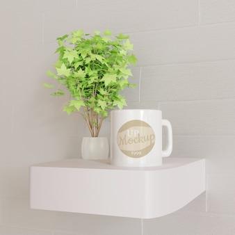 Maqueta de taza blanca en escritorio de pared blanca con planta decorativa