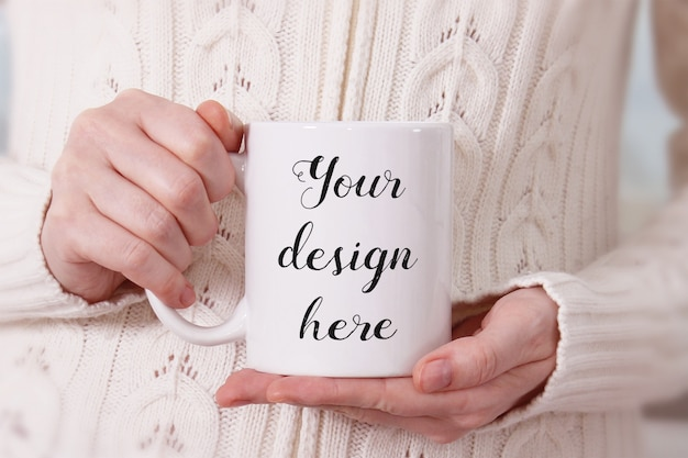 Maqueta de una taza de café con leche en manos de la mujer