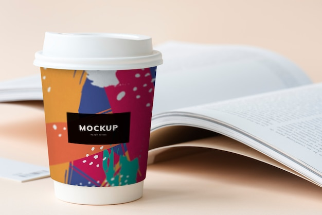 Maqueta de la taza de café para llevar en una mesa con un libro abierto