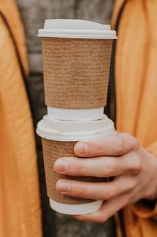 Maqueta de tazas de café recicladas psd con primer plano de la mano