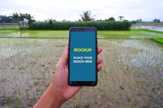 Maqueta de teléfono inteligente junto al campo