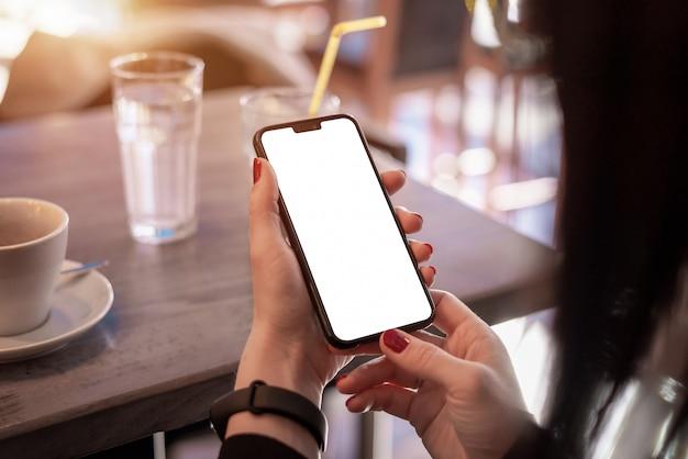 Maqueta de teléfono inteligente en manos de mujer. concepto de uso de la aplicación del teléfono y pulsera inteligente