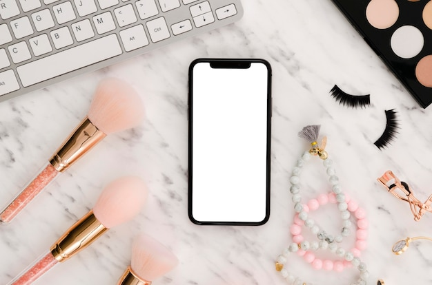 Maqueta de teléfono inteligente plana con pinceles de maquillaje