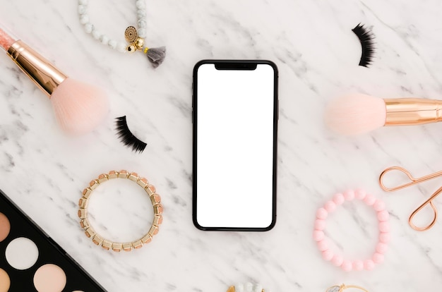 Maqueta de teléfono inteligente plano con accesorios de maquillaje