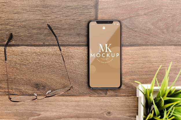 Maqueta de teléfono inteligente plano con gafas en el escritorio
