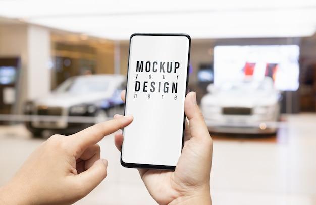 Maqueta de teléfono inteligente en la sala de exposición de automóviles de lujo