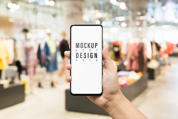 Maqueta de teléfono inteligente en la tienda de moda de ropa femenina