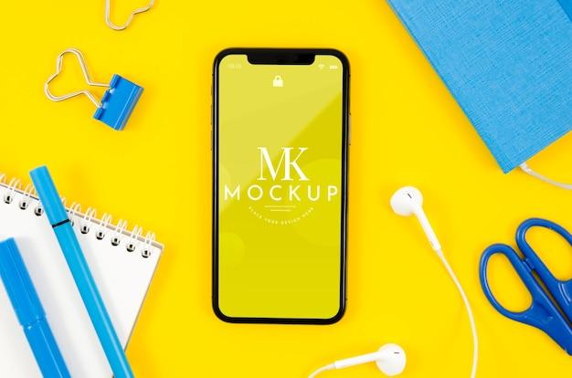 Maqueta de teléfono inteligente de vista superior con auriculares y material de oficina